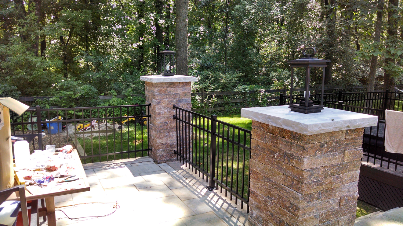 custom stone pillars with landscape lighting and aluminum fencing connected