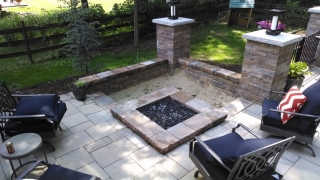 custom square fire pit in corner bordered by lawn chairs and retaining walls