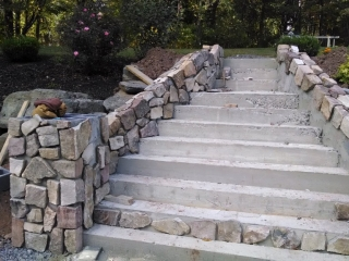 hardscaping crew installing stonework to concrete steps