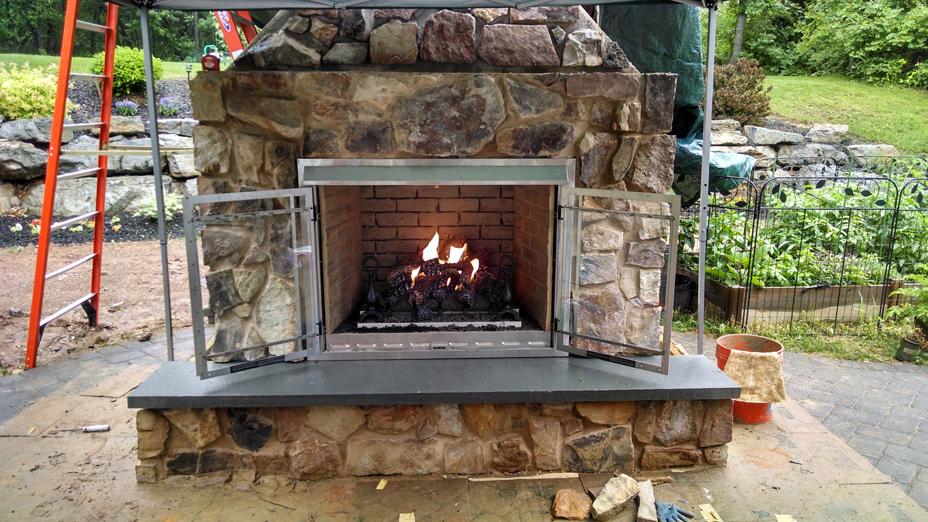 outdoor fireplace with fire burning inside