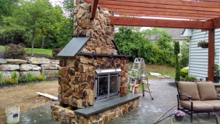 closeup of outdoor stone fireplace in backyard patio
