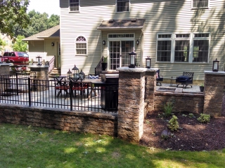 retaining walls with landscape lighting and aluminum fencing