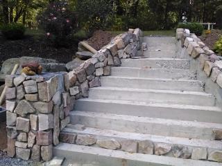 hardscaping crew installing stonework to concrete steps